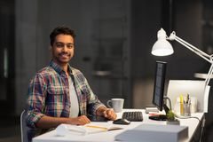 Designer with computer working at night office stock photography