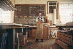 Designer craftsman standing confidently in his workshop Stock Photo