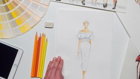 Designer creates a sketch using paints for the magazine. Close up. Time lapse stock footage