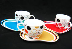 Designer Cups and Saucers. Nice designer colored porcelain cups placed on heart shaped saucers Royalty Free Stock Image