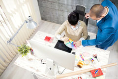 Designer with customer in design studio. Young female with customer in design studio royalty free stock images
