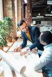 Designer de interiores que sentem alegres ao cooperar no projeto imagem de stock