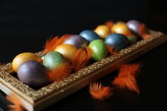 Easter painted chicken eggs. Designer decorated chicken eggs for Easter on a gold textured tray on black backgroundn royalty free stock photos