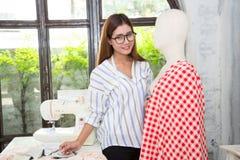 Designer der jungen Frau, der arbeitet am Studio auf Kleid auf Damenschneiderin ` Stockfotografie