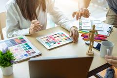 Designer der jungen Frau, der mit Tablettenfarbproben für Auswahl auf Schreibtisch arbeitet stockfoto