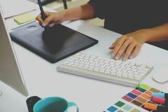 Designer, der mit digitaler Tablette und Laptop-Computer am Schreibtisch arbeitet Stockbilder
