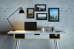 Designer desk with empty laptop. Close up of creative designer desk with blank laptop, coffee cup, lamp, picture frames and other items on white brick wall Stock Image