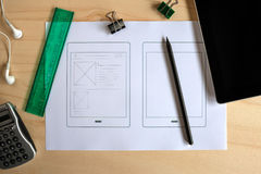 Designer desk with paper prototype of a tablet application. View from above Royalty Free Stock Photo