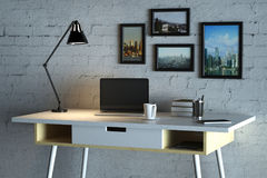 Designer desktop with empty laptop computer. Close up of creative designer desktop with blank laptop computer, coffee cup, lamp, picture frames and other items Royalty Free Stock Photo