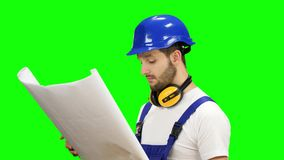 Designer with the drawing in his hands object and looks around. Green screen. Designer in a helmet and gloves with a drawing in his hands object and looks around stock footage