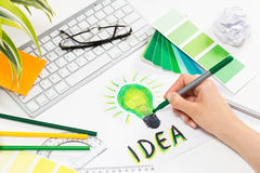 Designer drawing a light bulb. Brainstorming cocnept. Royalty Free Stock Photo