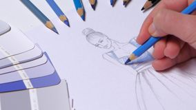 Designer dress decorates a sketch in blue, on a table cloth samples lie. Close up