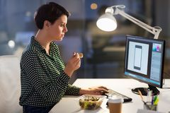Designer eating and working at night office. Business, overwork, deadline and people concept - graphic designer at computer eating salad at night office royalty free stock photography