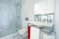 Designer en-suite bathroom with shower cabin. Designer contemporary en-suite bathroom with large shower cabin, modern wash basin, towels and toilet with marble stock photo