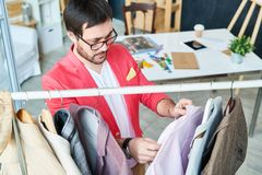 Designer exploring clothes on hangers royalty free stock image
