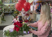 Designer florist makes a bouquet of red roses for Valentine`s day on the background of the interior of a flower shop.  stock photos