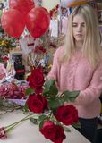 Designer florist makes a bouquet of red roses for Valentine`s day on the background of the interior of a flower shop.  stock photo