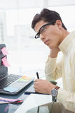 Designer with glasses thinking and using digitizer. In his office Stock Images