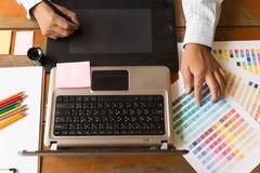 designer gráfico autônomo que usa a tabuleta digital, computador, homem w imagem de stock