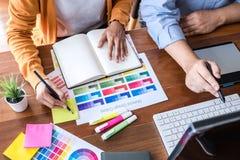 Designer gráfico criativo de dois colegas que trabalha na seleção de cor e nas amostras de folha da cor, tirando na tabuleta de g foto de stock