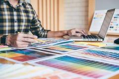 Designer gráfico criativo novo que usa a tabuleta de gráficos ao choosin imagem de stock