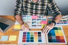 Designer gráfico criativo novo que usa a tabuleta de gráficos a escolher a carta das amostras da amostra de folha da cor para a c fotos de stock