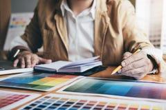 Designer gráfico criativo novo que usa a tabuleta de gráficos a escolher a carta das amostras da amostra de folha da cor para a c imagem de stock