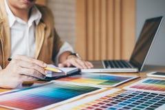 Designer gráfico criativo que usa a tabuleta de gráficos a escolher a carta das amostras da amostra de folha da cor para a colora imagem de stock royalty free