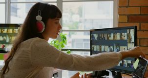 Designer gráfico fêmea que escuta a música ao trabalhar na mesa 4k filme