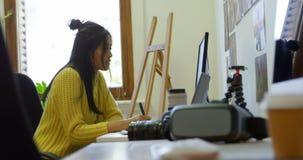 Designer gráfico fêmea que trabalha na mesa 4k video estoque