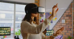 Designer gráfico fêmea que usa auriculares da realidade virtual em um escritório moderno 4k filme