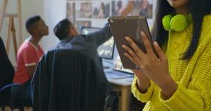 Designer gráfico fêmea que usa a tabuleta digital no escritório 4k filme