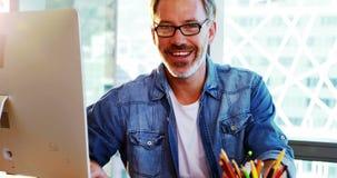 Designer gráfico masculino feliz que usa a tabuleta gráfica na mesa video estoque