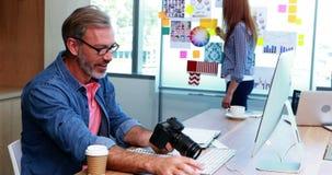 Designer gráfico masculino que trabalha na mesa video estoque