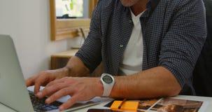 Designer gráfico masculino que trabalha no portátil na mesa 4k filme