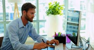 Designer gráfico masculino que trabalha sobre a tabuleta gráfica em sua mesa vídeos de arquivo