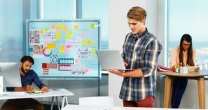 Designer gráfico masculino que usa o portátil no escritório vídeos de arquivo
