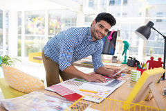 Designer gráfico masculino que usa o telefone celular ao trabalhar na mesa fotografia de stock royalty free