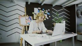 Designer gráfico novo com o cabelo curto que trabalha no computador usando a tabuleta filme