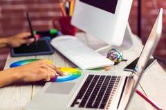 Designer gráfico que trabalha com carta e digitador de cor Fotos de Stock Royalty Free