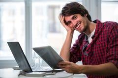 Designer gráfico que usa o portátil e a tabuleta digital em sua mesa Fotos de Stock Royalty Free