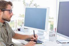 Designer gráfico que usa a tabuleta de gráficos Imagens de Stock