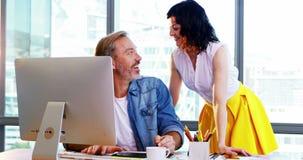 Designer gráficos masculinos e fêmeas que trabalham junto na mesa vídeos de arquivo