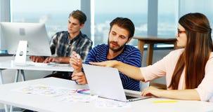 Designer gráficos que discutem sobre o portátil na mesa filme