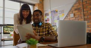 Designer gráficos que trabalham junto na tabuleta digital na mesa no escritório 4k filme