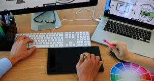 Designer gráficos que trabalham na mesa video estoque