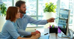 Designer gráficos que trabalham sobre o computador na mesa vídeos de arquivo