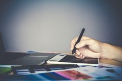 Designer in tartan shirt graphic creative working on Mouse pen laptop in office royalty free stock image
