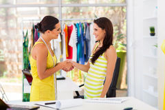 Designer greeting client. Friendly fashion designer greeting client in studio Royalty Free Stock Images