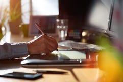 Designer gráfico que trabalha com a tabuleta e a pena digitais do desenho Imagens de Stock